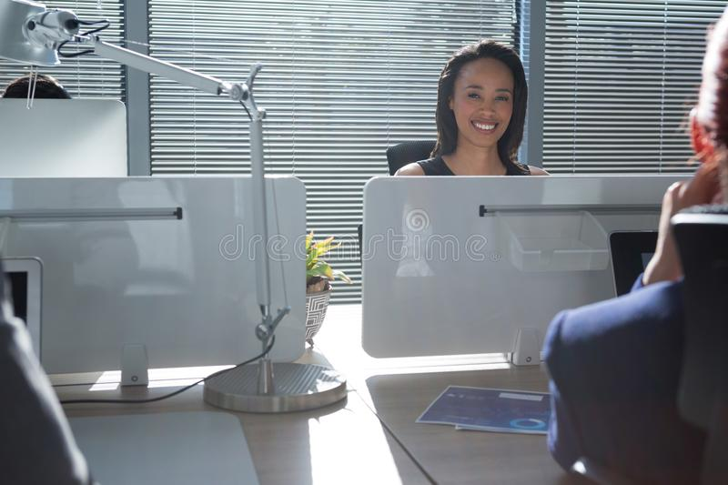 Smiling executive sitting in the office royalty free stock photos
