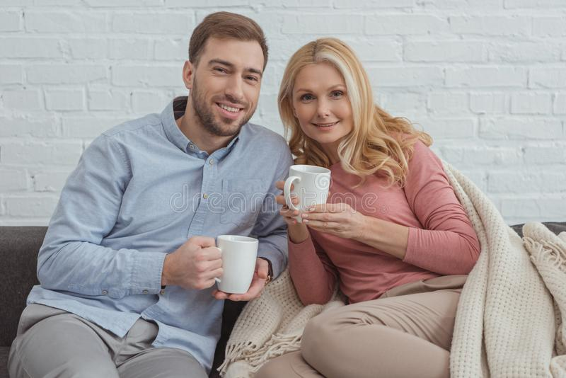portrait of smiling family with cups of coffee resting stock photography