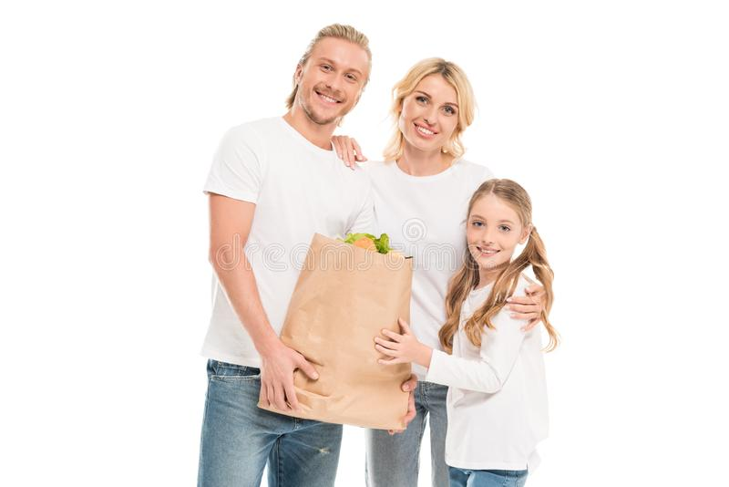 portrait of smiling family holding paper bag with food and looking at camera royalty free stock photo
