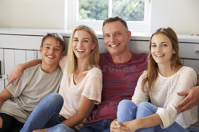 Portrait Of Smiling Family Relaxing On Seat At Home stock photos