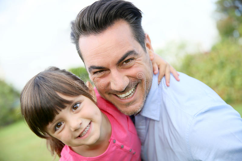 Portrait of smiling father with daughter in his arms stock images