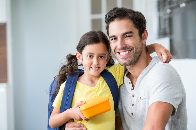 Portrait of smiling father and daughter with lunch box. At home stock image