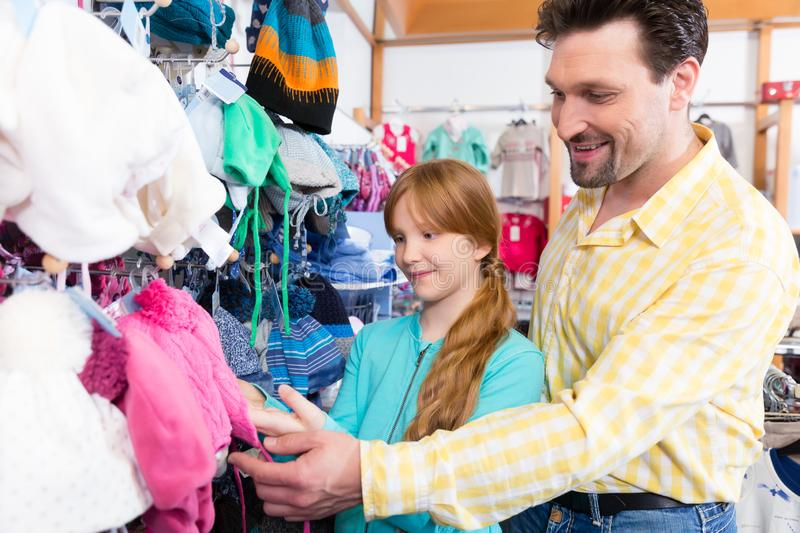 Father and daughter shopping clothes in retail store stock images