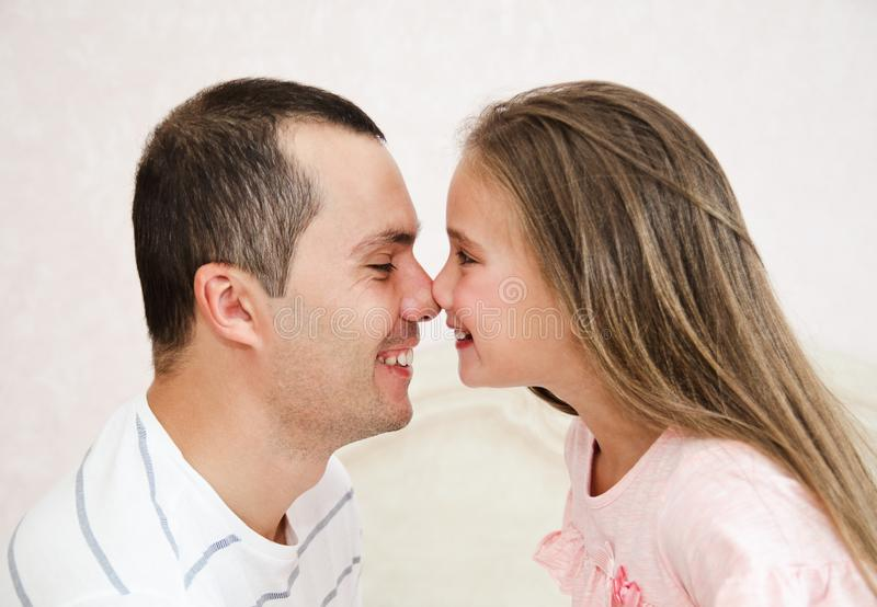 Portrait of smiling father with his little daughter child sharing love. And having fun at home stock photography