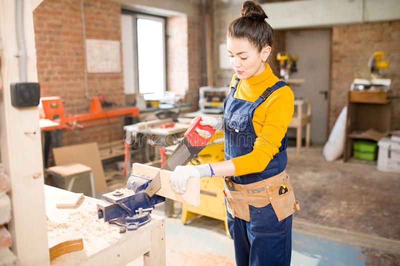 Young Woman Cutting Wood royalty free stock image