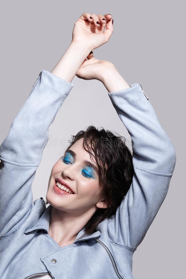 Portrait of smiling female in blue jacket with hands up. Woman with unusual beauty makeup and wet hair, and blue shadows make-up royalty free stock photos