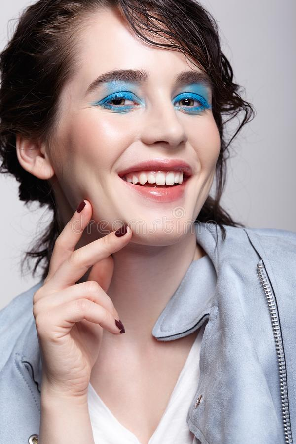 Portrait of smiling female in blue jacket. Woman with unusual beauty makeup and wet hair, and blue shadows make-up stock images