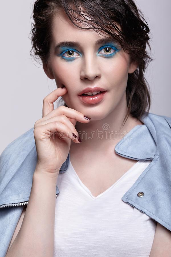 Portrait of smiling female in blue jacket. Woman with unusual beauty makeup and wet hair, and blue shadows make-up royalty free stock image