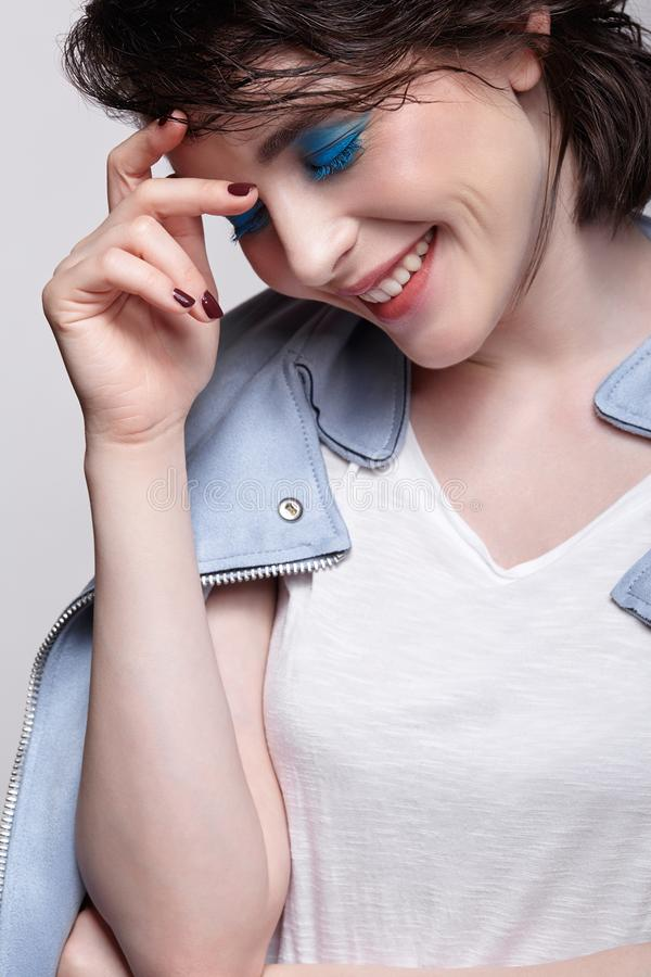 Portrait of smiling female in blue jacket. Woman with unusual beauty makeup and wet hair, and blue shadows make-up stock photos