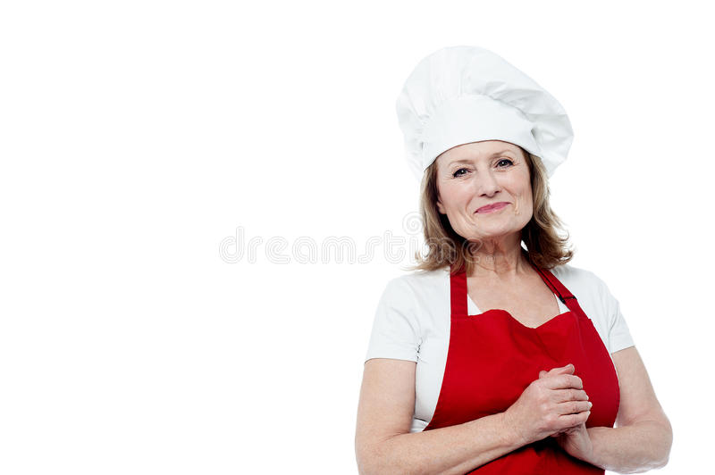 Portrait of a smiling female chef, hands clasped royalty free stock photography