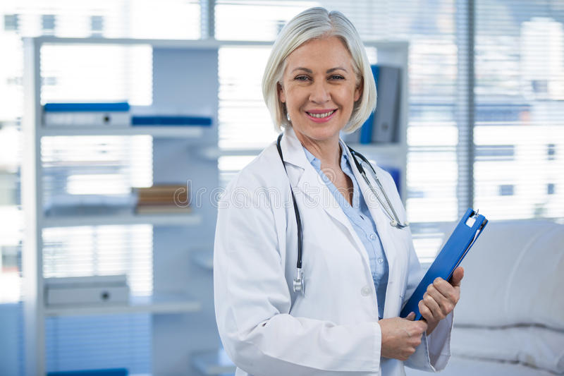 Portrait of a smiling female doctor holding clipboard royalty free stock photo