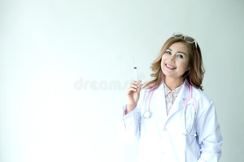 Portrait of smiling female doctor with injection needle. Friendly young woman doctor with a stethoscope around on neck. asia. royalty free stock photo
