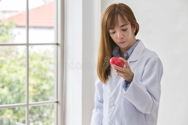 Portrait of smiling female doctor with red heart. Friendly young woman doctor with red heart on hand. Selective focus stock photo