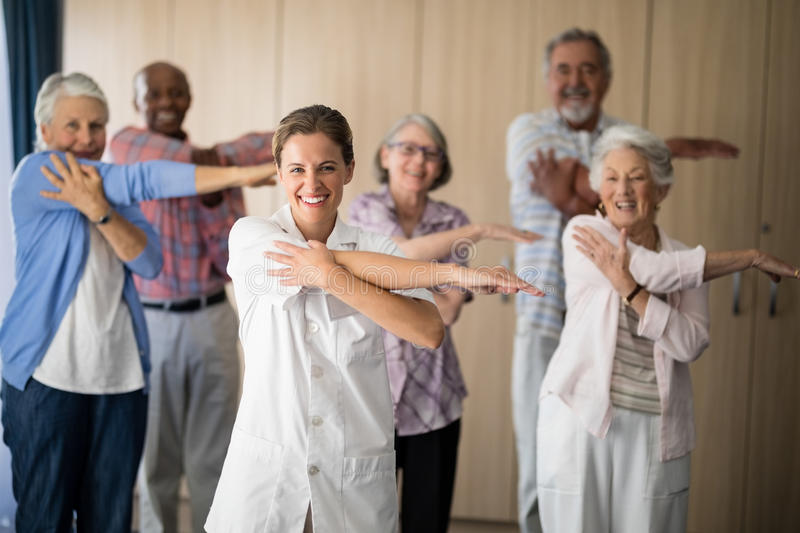 Portrait of smiling female doctor and seniors stretching arm against wall. At retirement home royalty free stock photo