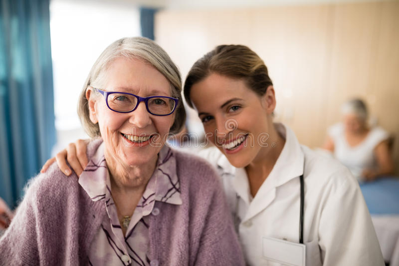Portrait of smiling female doctor standing arm around senior woman stock photography
