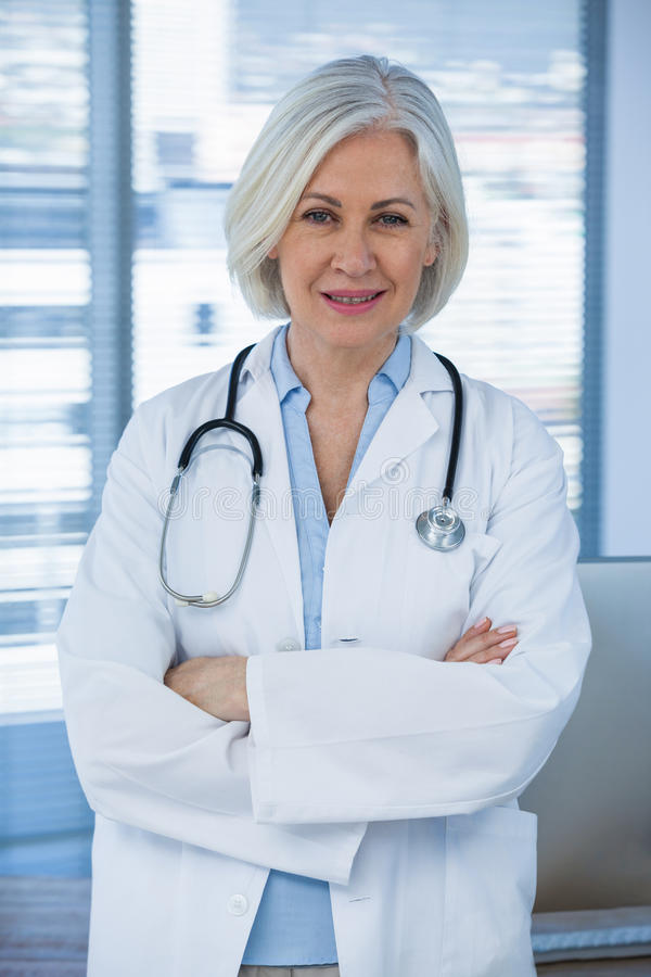 Portrait of a smiling female doctor standing with arms crossed royalty free stock image