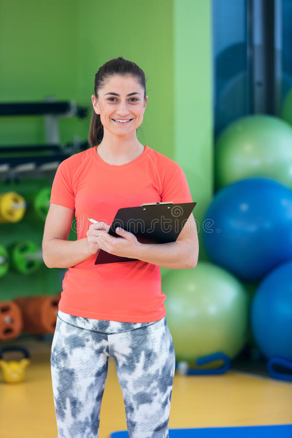 Portrait of smiling female fitness instructor writing in clipboard while standing in gym royalty free stock images