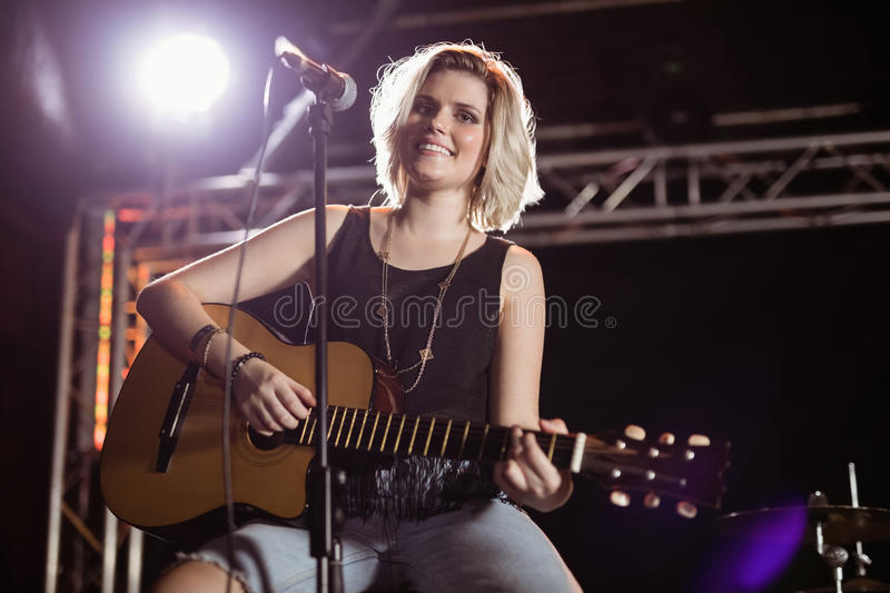 Portrait of smiling female guitarist playing guitar at nightclub stock image