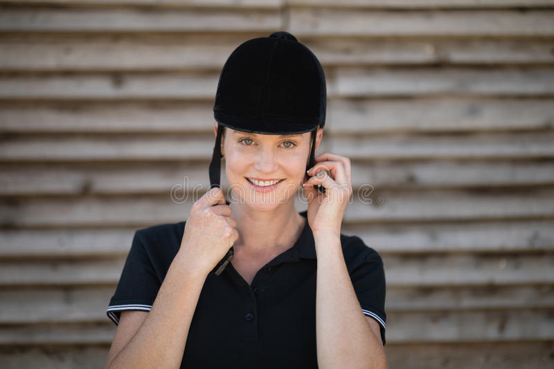 Portrait of smiling female jockey adjusting sports helmet stock image