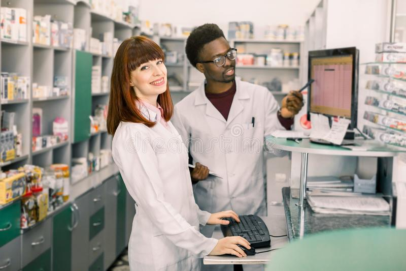 Portrait of a smiling female pharmacist standing in interior of the modern pharmacy, male colleague working with stock photo