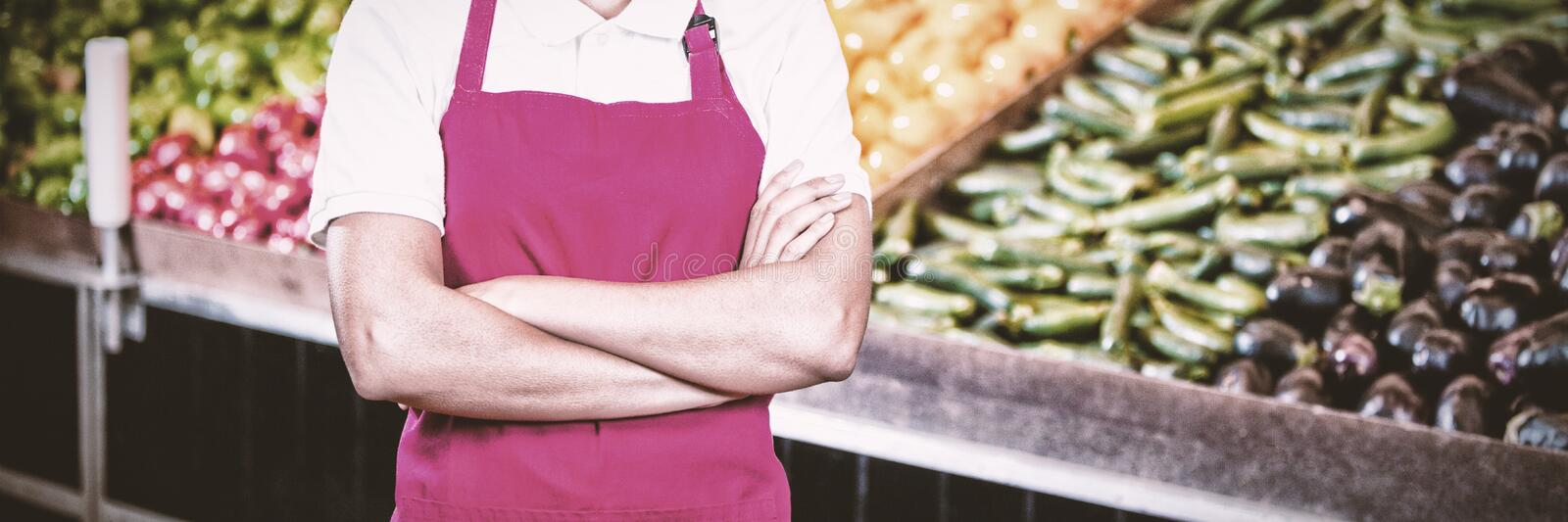 Portrait of smiling female staff standing with arms crossed in organic section. Of super market royalty free stock photos