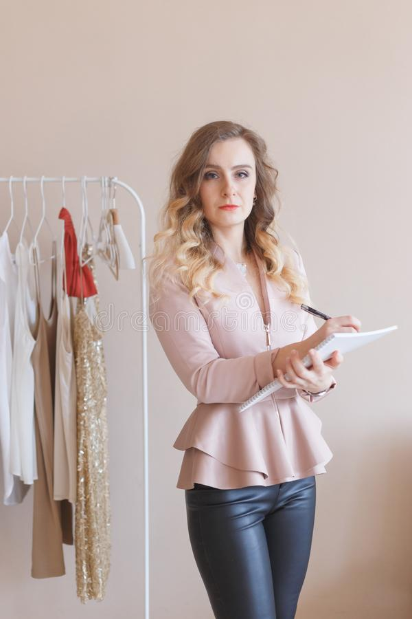 Portrait of smiling female store owner with a diary. Dress designer working in her boutique. stock photo