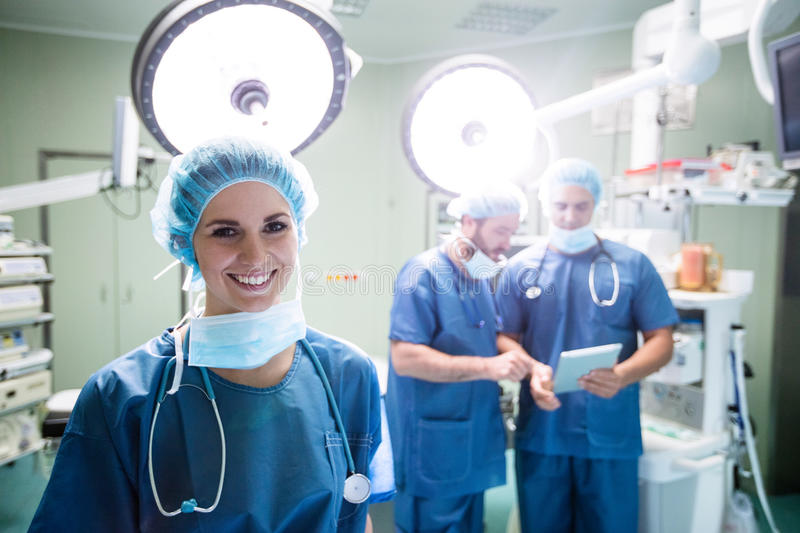 Portrait of smiling female surgeon standing in operation room stock photography