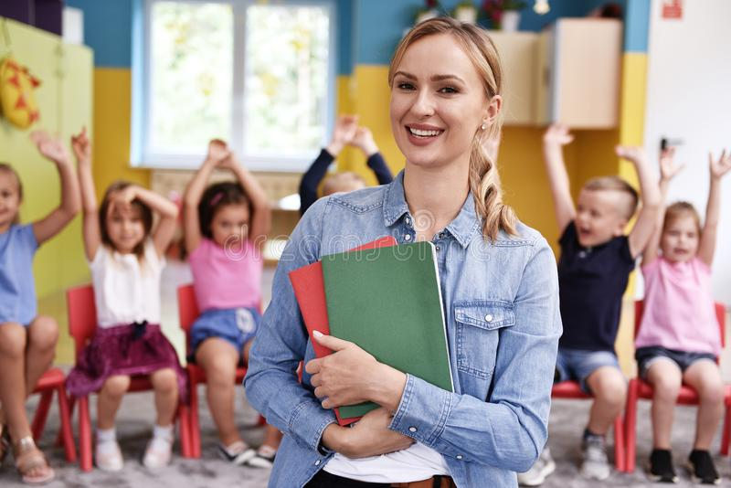 Smiling female teacher in the preschool. Portrait of smiling female teacher in the preschool and children in the background royalty free stock photography
