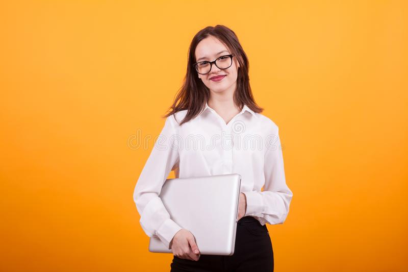 Portrait of a smiling female teenager standing with laptop in her hands over yellow background royalty free stock photos
