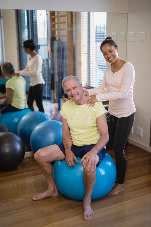 Portrait of smiling female therapist giving neck massage to senior patient sitting on exercise ball. Against mirror at hospital ward royalty free stock image
