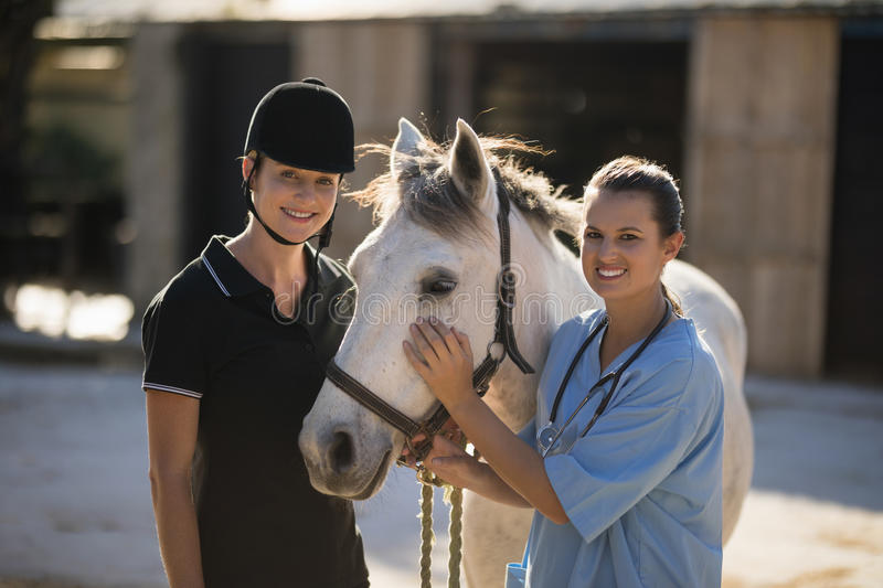 Portrait of smiling female vet with jockey standing by horse stock images