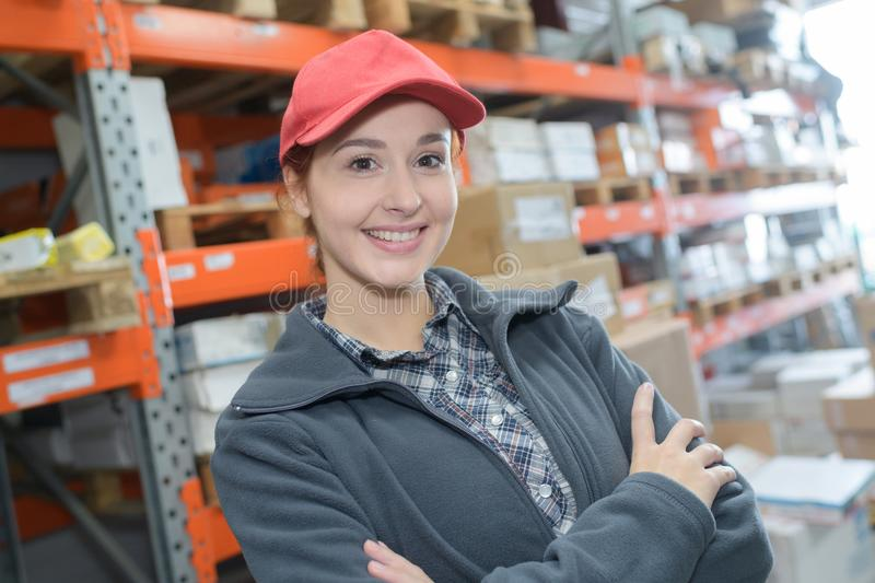 Portrait smiling female worker with arms crossed in warehouse royalty free stock photography
