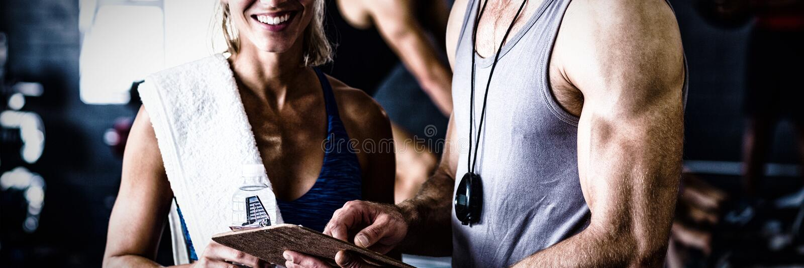 Portrait of smiling fitness instructor with woman in gym stock images