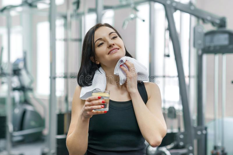 Portrait of smiling fitness woman with glass of water with lemon, woman in sportswear after fitness classes drinking water in gym stock photo