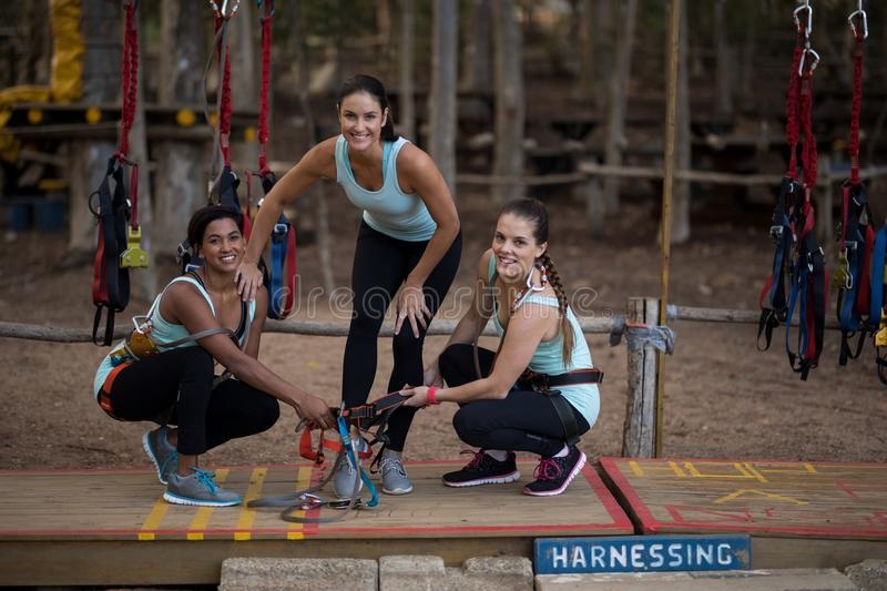 Smiling friends wearing harness in park stock image