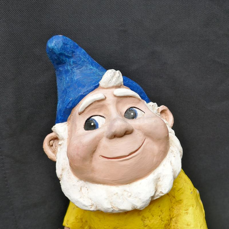Portrait of a smiling garden gnome with blue hat, white beard and yellow jacket in front of black background stock photo