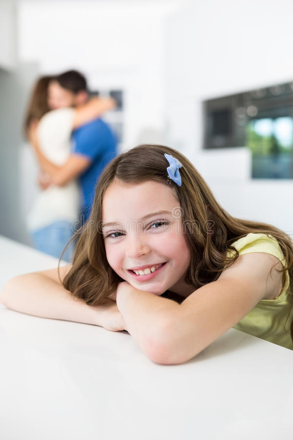 Portrait of smiling girl against embracing parents stock image