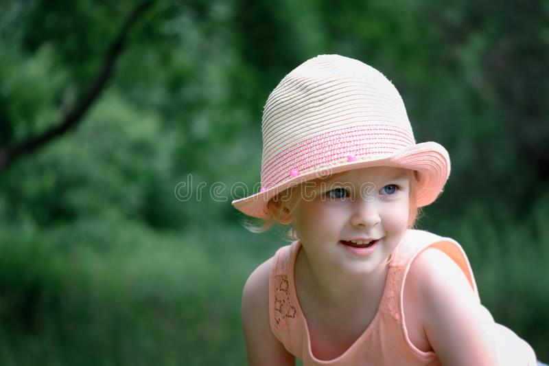 Portrait of a smiling girl. A cute baby in a straw hat. stock images