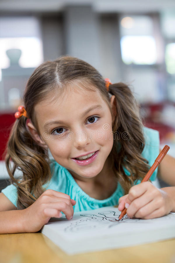 Portrait of smiling girl drawing sketch on book. At home royalty free stock photos