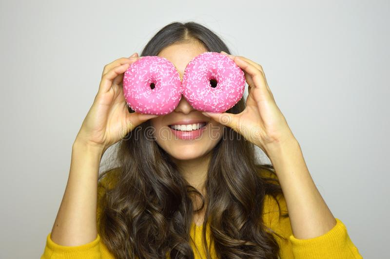 Portrait of smiling girl having fun with sweets isolated on gray background. Attractive young woman with long hair posing with dou royalty free stock photo