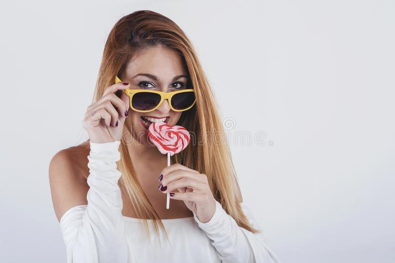 Portrait of smiling girl with heart shaped lollipop. On white background stock images