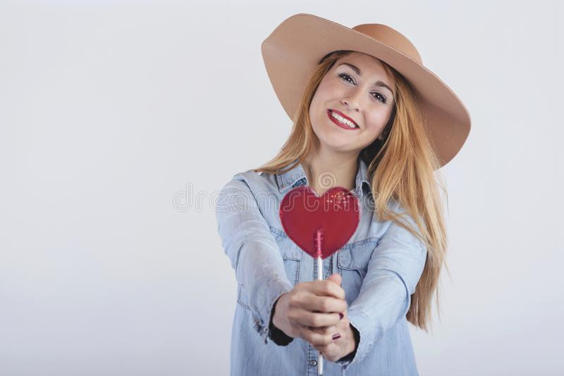 Portrait of smiling girl with heart shaped lollipop. On white background stock photos