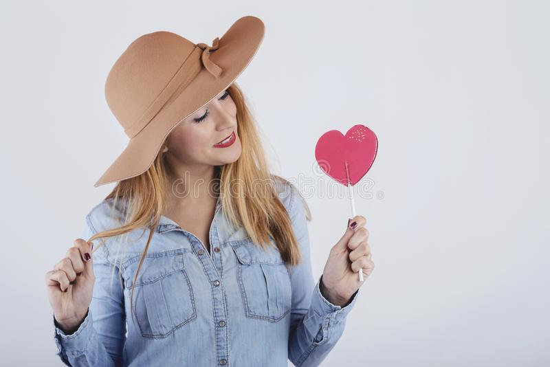 Portrait of smiling girl with heart shaped lollipop. On white background stock image