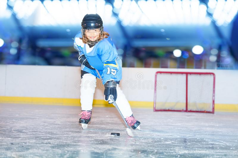 Happy girl passing the puck during hockey game. Portrait of smiling girl, ice hockey player, passing the puck during game on the rink stock photo
