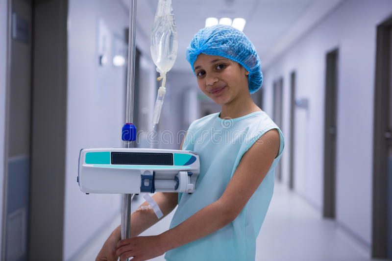 Portrait of smiling girl with iv drip standing in corridor royalty free stock photography