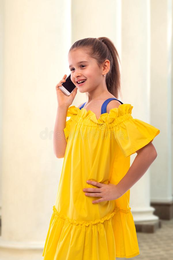 Portrait of a smiling girl with long hair  talking on the phone.  She walks past classic white columns stock images