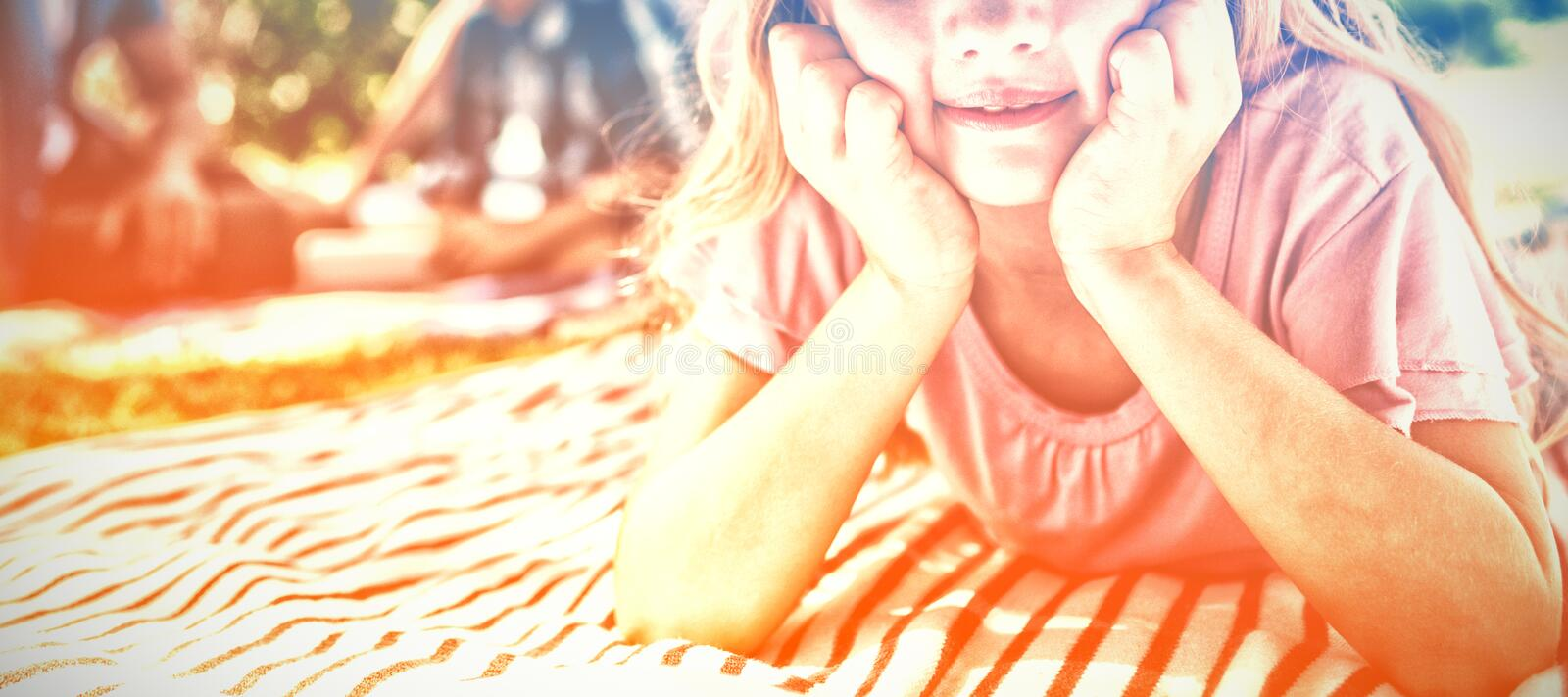 Smiling girl lying on blanket while family sitting in background royalty free stock photography