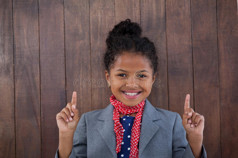 Portrait of smiling girl pretending as businesswoman pointing upwards stock image