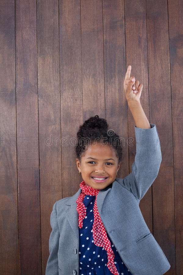 Portrait of smiling girl pretending as businesswoman standing with arms raised stock images