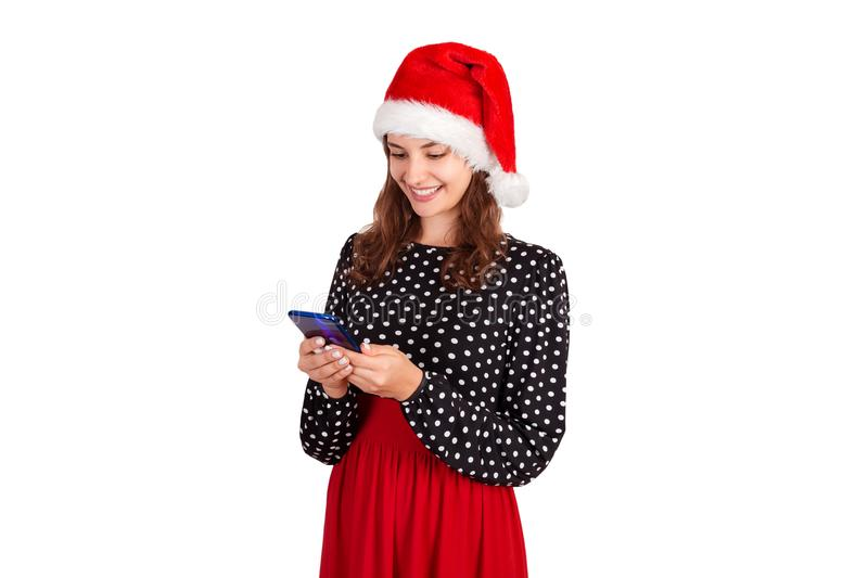 Portrait of a smiling girl standing and texting on mobile phone. emotional girl in santa claus christmas hat isolated on white bac stock photo